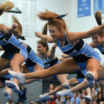 The varsity cheerleaders perform a routine with a series of jumps at the fall pep assembly. Photo by Katherine Odell