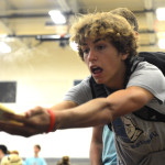 Freshman Peter Kohring reaches over the hot griddle to catch a flying pancake that fell short. Photo by Annie Lomshek