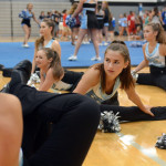 Sophomore and Varsity Lancer Dancer Megan Walstrom stretches with her team in preparation for their performance. Photo by Ellie Thoma