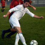 Senior Grayson Rapp plays the ball through to his  fellow strikers. Photo by Audrey Kesler