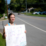 Junior Isabel Epstein waves a sign encouraging drivers to visit the bake sale. Photo by Caroline Mills