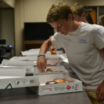 Sophomore class president, Dane Erickson coming in to the student council retreat, and grabbing a doughnut. Photo by Morgan Plunkett