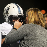 Athletic trainer, Megan Burki, talks to sophomore Isaiah Wright on the sideline aster he leaves the field. Photo by Kaitlyn Stratman