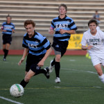 Junior Tommy Nelson sprints to dribble the ball up the field, leaving his opponent behind him. Photo by Kaitlyn Stratman