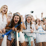 Seniors Sophie Thiede, Emma Henderson, and Claire Pottenger cheer with the rest of the senior girls at the front of the stands. Photo by Kaitlyn Stratman