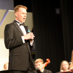 Orchestra conductor Mr. Keda addresses the audience about his experience at East so far. Photo by Elizabeth Anderson