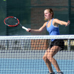 Sophomore varisty tennis player Lucy Kendall hits the ball while playing in a doubles match . Photo by Ellen Swanson