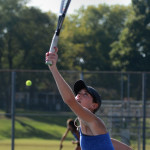Junior Caro Bush hits a serve in practice before her single match. Photo by Annie Lomshek