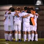 The boys varsity team huddles before going into the second half of the game. Photo by Annie Lomshek
