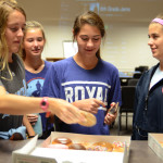 Senior, Hope Dunn, and freshmen Anna Parker and Gretchen Raedle grab some doughnuts on their way into the room. Photo by Grace Goldman