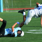 As he falls down, freshman Hatch McCray tackles and pulls down one of the freshman Rockhurst players. Photo by Grace Goldman
