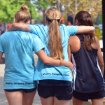 Seniors Carolyn Kinney, Hope Dunn, and Devon Dietrich walk down Mass Street, discussing the results of the day's race. Photo by Libby Wilson