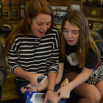 Junior Allison Benson and Sophomore Elise Baker grab some Oreos for another attempt on getting one from their forehead to their mouth. Photo by Izzy Zanone