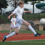 Freshman Seth Harnden kicks ball towards Shawnee Mission West goal, down the field. Photo by Ava Simonsen