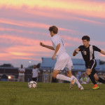 Sophomore Charlie Colby runs to dribble soccer ball away from SMNW player. Photo by Ava Simonsen