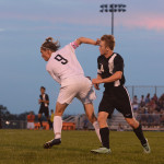 Senior Clayton Phillips jumps in front of Shawnee Mission North West player to steal the ball. Photo by Ava Simonsen