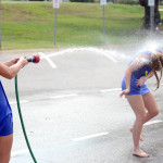 Junior Emma Linscott sprays sophomore Hannah Phillips with a hose during their lunch break. Photo by Maddie Smiley