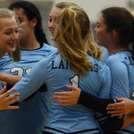 Sophomore Lily Taylor celebrates winning a point with her teammates during the second match. Photo by Sophie Storbeck