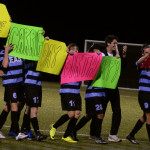 """The team surprises Carrie Morantz, team manager, by thanking her for her hard work and wishing her a happy birthday. Senior Porter Carroll later helped the boys rearrange the signs to read """"Happy Birthday Carrie.""""  Photo by Sophie Storbeck"""