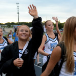 Junior Mya Hutcherson smiles and waves to friends as she enters the game. Photo by Ellie Thoma