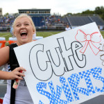 Senior Caroline Kessinger laughs and shows off her poster to the crowd as she enters the game. Photo by Ellie Thoma