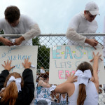 Seniors Alex Masson and Troy Shackelford help Junior Mya Hutcherson and Senior Rachel Rodgers tape posters up on the fence. Photo by Ellie Thoma