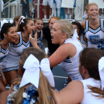 Senior Caroline Kessinger stands in the middle of the cheerleaders making a go-pro video while they chant. Photo by Ellie Thoma