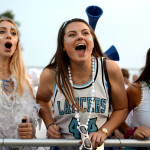 Seniors Sophie Thiede, Emma Henderson, and Emory Foster cheer as loud as they can from the stands. Photo by Ellie Thoma