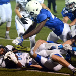 Senior Nigil Houston clings to the ball after being knocked down by Rockhurst defense. Photo by Ellie Thoma