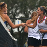 Seniors Quincy Bair and Camille Moore shake their opponents hands after their doubles match. Photo by Morgan Plunkett