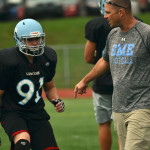 Coach May instructs junior Justin Schuman. Photo by Morgan Plunkett