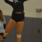 Senior Sara Maddox practices serving in the warmups before the game. Photo by Izzy Zanone