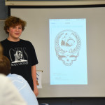 Senior Peter McDonald speaks to the class about their new T-shirts for the club. Photo by Ava Simonsen