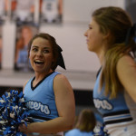 Senior cheerleader Tyler Lockton laughs at Maggie Gray as they cheer on the sidelines. Photo by Katherine Odell