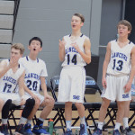 The Boy's Freshman team on the bench react to Freshman Luke Hanson's successful shot. Photo by CJ Manne